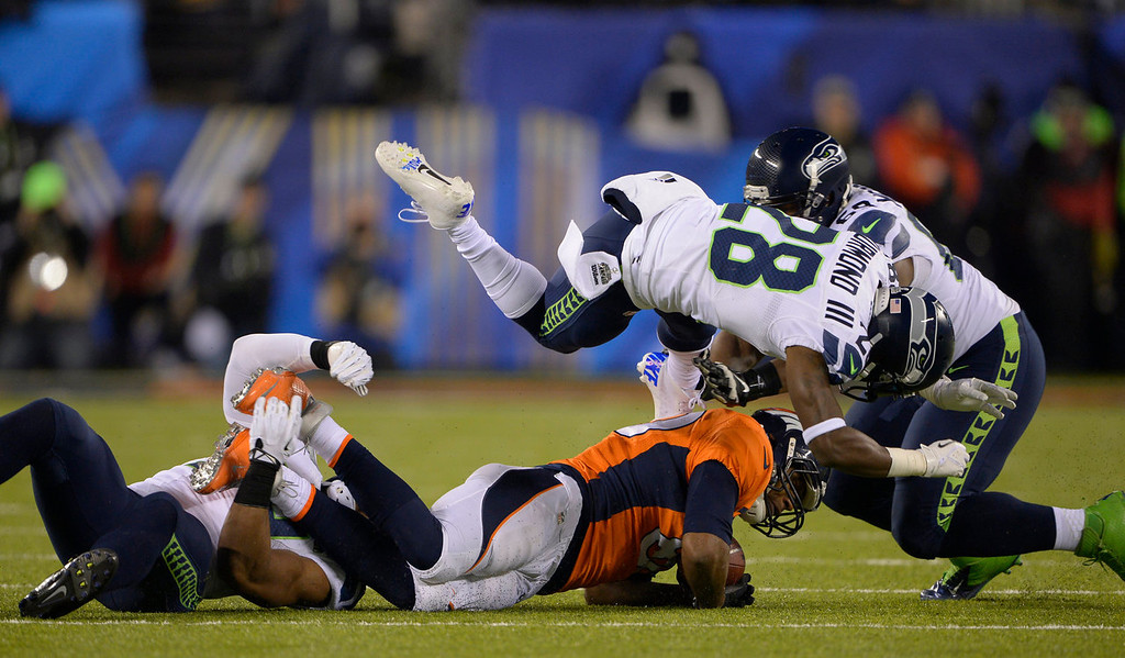 . Denver Broncos tight end Julius Thomas (80) gets pummeled after a catch during the first quarter. The Denver Broncos vs the Seattle Seahawks in Super Bowl XLVIII at MetLife Stadium in East Rutherford, New Jersey Sunday, February 2, 2014. (Photo by Joe Amon/The Denver Post)