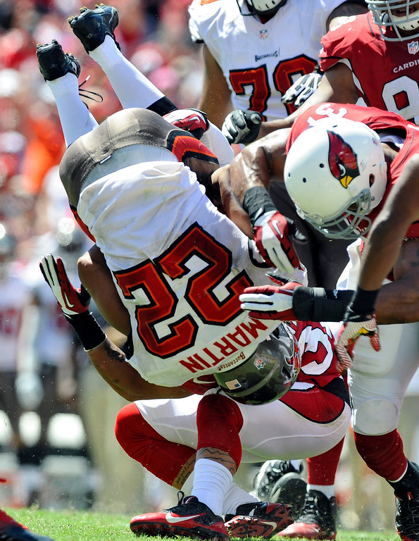 . Tampa Bay Buccaneers running back Doug Martin (22) is sent flying on a hit by Arizona Cardinals defensive back Tyrann Mathieu (32) and strong safety Yeremiah Bell (37) during the first quarter of an NFL football game Sunday, Sept. 29, 2013, in Tampa, Fla. (AP Photo/Brian Blanco)