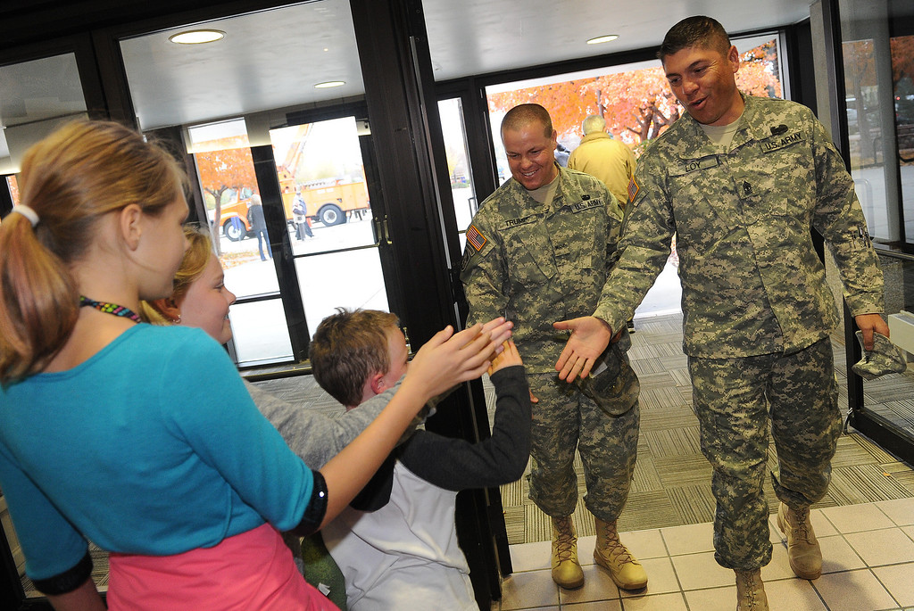 . LONGMONT, CO - OCTOBER 29:   Jeremy Trump, middle and Raymond Loy, right, both of the Utah National Guard, get high fives from Jordynn Lee, left and Emma Lee Taylor and her brother Benjamin as they arrive at the Life Bridge Community Church in  Longmont, Co on October 29, 2013.  They were coming to be part of a celebration  held to thank members of the military, law enforcement, firefighters and members of Colorado Department of Transportation for all their work during and after the floods.   (Photo By Helen H. Richardson/ The Denver Post)