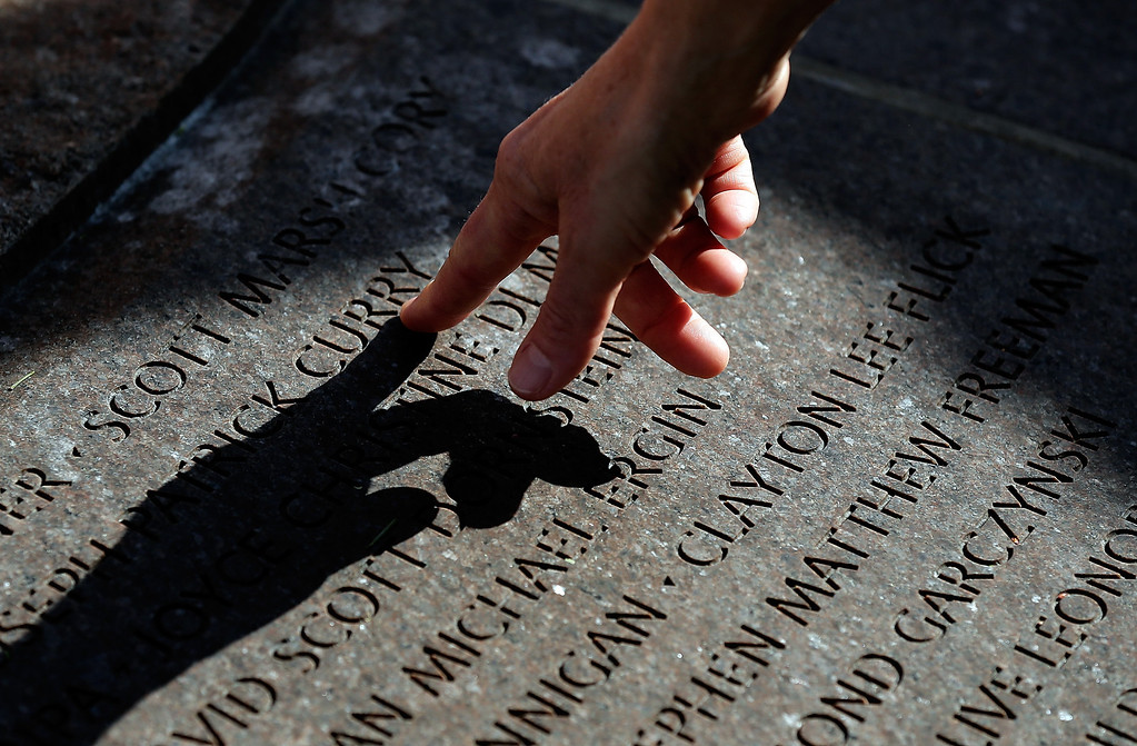 . A person reaches to touch the names of loved ones carved into the base of a cairn during a remembrance ceremony for those who died on Pan Am Flight 103 at Arlington National Cemetery December 21, 2013 in Arlington, Virginia.  (Photo by Win McNamee/Getty Images)