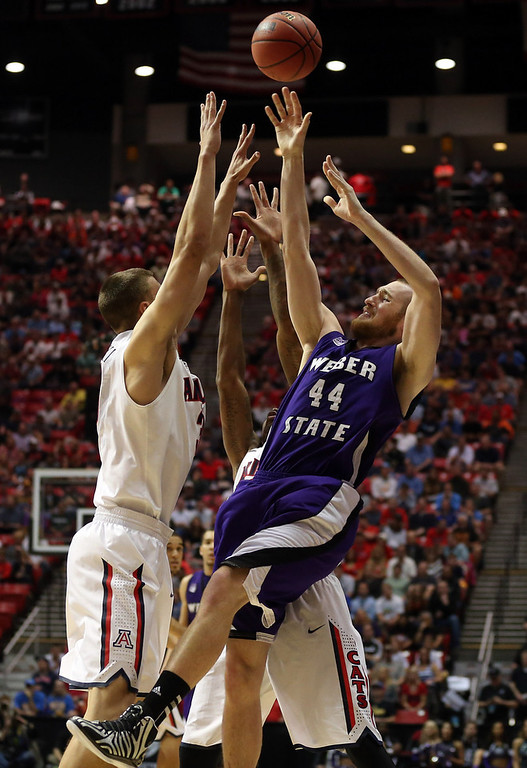 . Kyle Tresnak #44 of the Weber State Wildcats is covered by Kaleb Tarczewski #35 and Nick Johnson #13 of the Arizona Wildcats during the second round of the 2014 NCAA Men\'s Basketball Tournament at Viejas Arena on March 21, 2014 in San Diego, California.  (Photo by Jeff Gross/Getty Images)