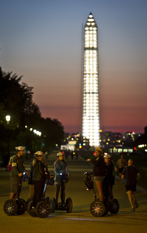 ". Tourists on ""Segways\"" are seen on the National Mall before the illuminated Washington Monument on the eve of a possible government shutdown as Congress battles out the budget in Washington, DC, September 30, 2013. In case of a government shutdown most of the tourist attractions in the US capital will be closed to visitors. AFP PHOTO / MLADEN ANTONOV/AFP/Getty Images"
