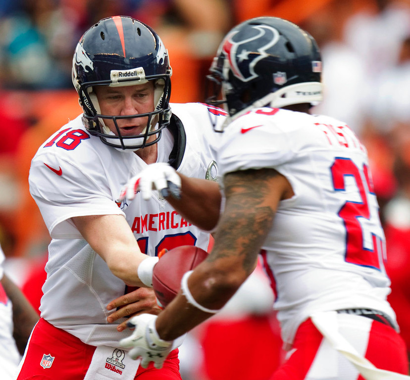 . Denver Broncos quarterback Peyton Manning (18) hands off the football to Houston Texans running back Arian Foster (23) of the AFC in the first quarter of the NFL football Pro Bowl game against the NFC in Honolulu, Sunday, Jan. 27, 2013. (AP Photo/Eugene Tanner)