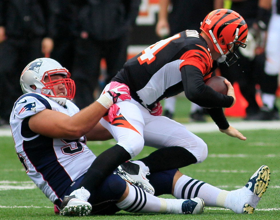 . Cincinnati Bengals quarterback Andy Dalton (14) is sacked by New England Patriots defensive tackle Chris Jones in the first half of an NFL football game, Sunday, Oct. 6, 2013, in Cincinnati. (AP Photo/Tom Uhlman)