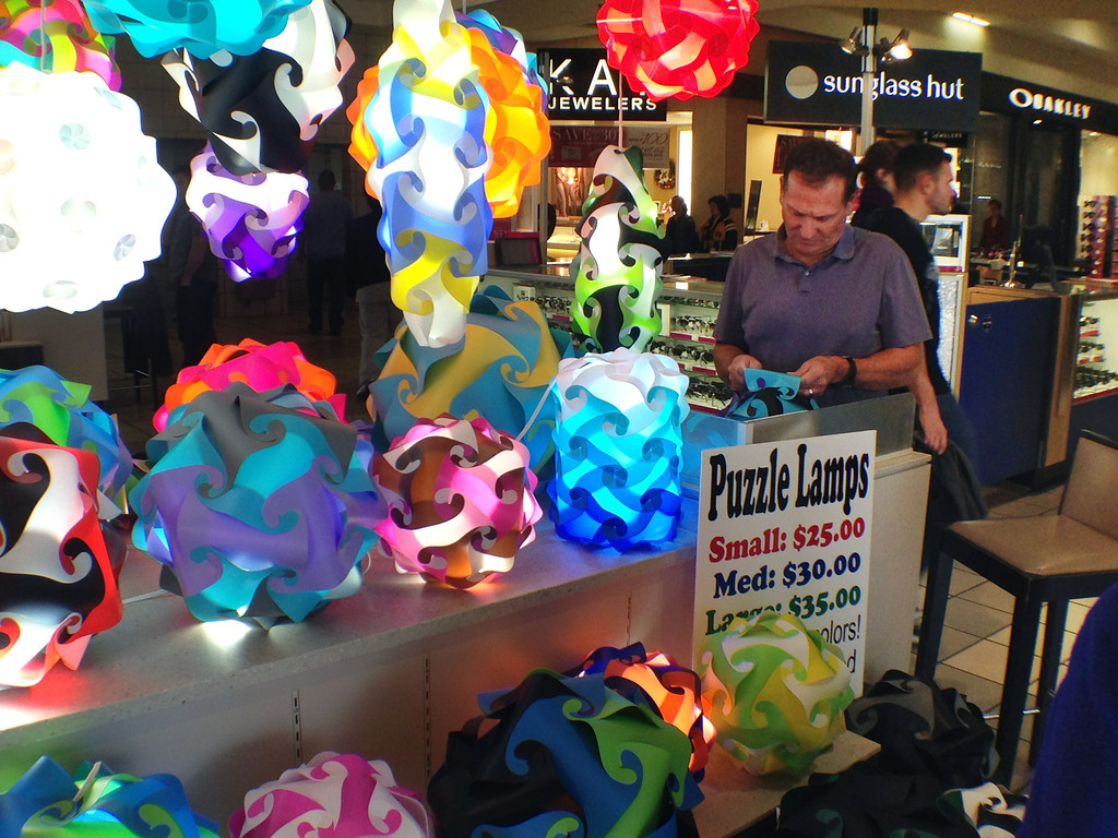 . Mark Martin, owner of the Sundance Company, is shown selling his Puzzle Lamps on Friday Nov. 29, 2013 at the Coronado Mall in Albuquerque, N.M. Thousands of shoppers in New Mexico joined the army of bargain hunters nationwide who searched to find Black Friday deals. (AP Photo/Russell Contreras)