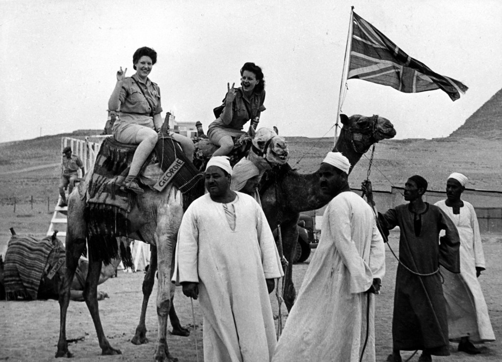 . 17th May 1945:  Girls from Britain\'s Auxiliary Territorial Services girls flaunt the \'V for Victory\' sign as they ride on camels during the V-Day celebrations in Cairo.  (Photo by G. Packham/Fox Photos/Getty Images)