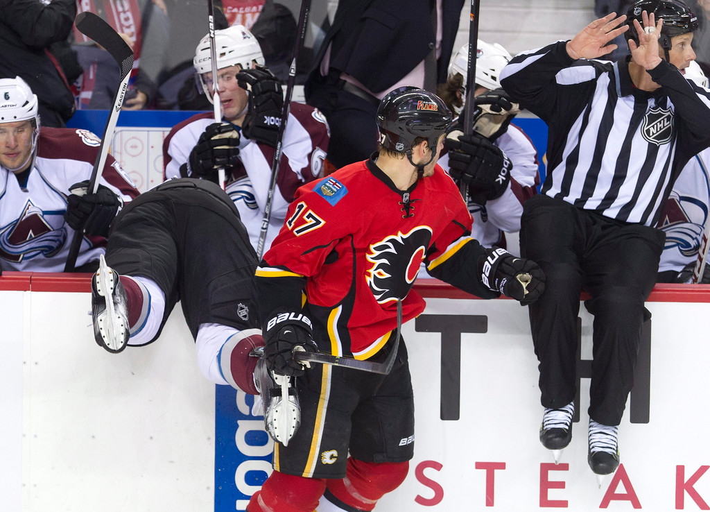 . Colorado Avalanche\'s Nick Holden, left, is knocked into the Colorado bench by Calgary Flames\' Lance Bouma during the first period of an NHL hockey game, Friday, Dec. 6, 2013 in Calgary, Alberta. (AP Photo/The Canadian Press, Larry MacDougal)