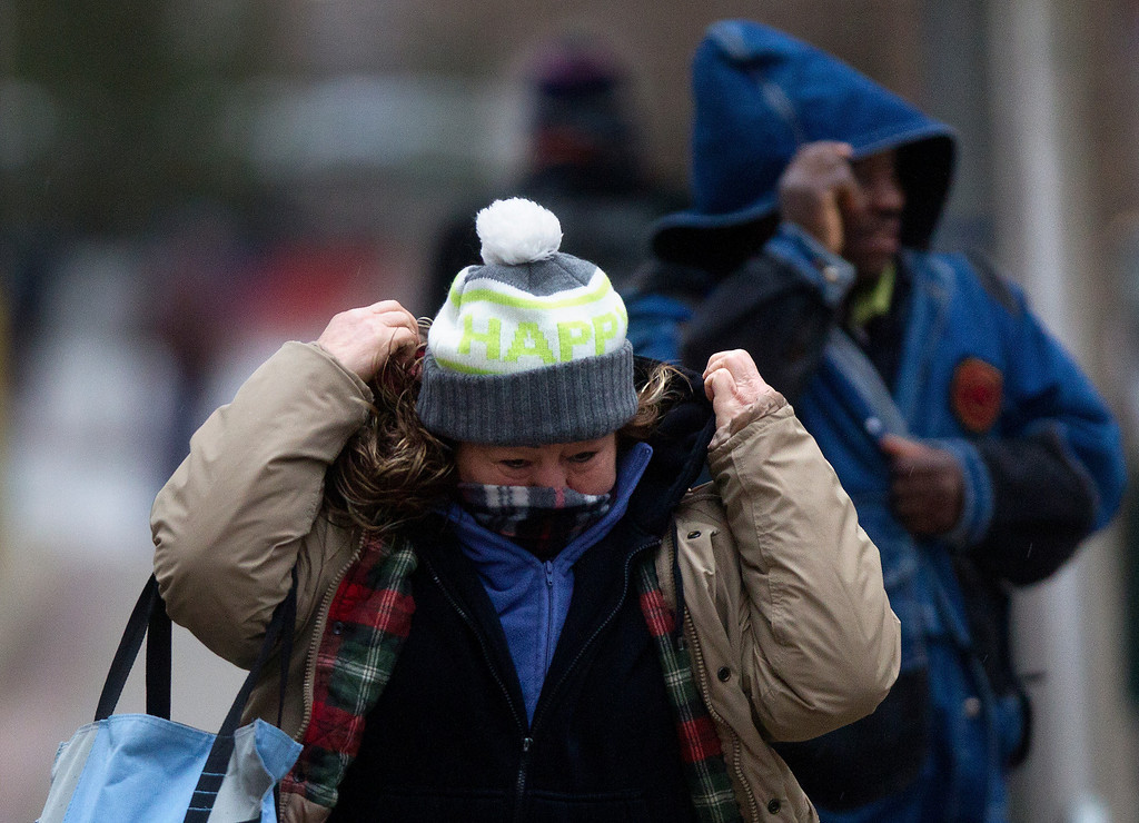 ". Berta Sosa adjusts her coat as she crosses Walker Street on her way to work, Tuesday, Jan. 28, 2014, in Houston. ""I\'m very cold and it\'s only going to get worse,\"" she said. (AP Photo/Houston Chronicle, Cody Duty)"