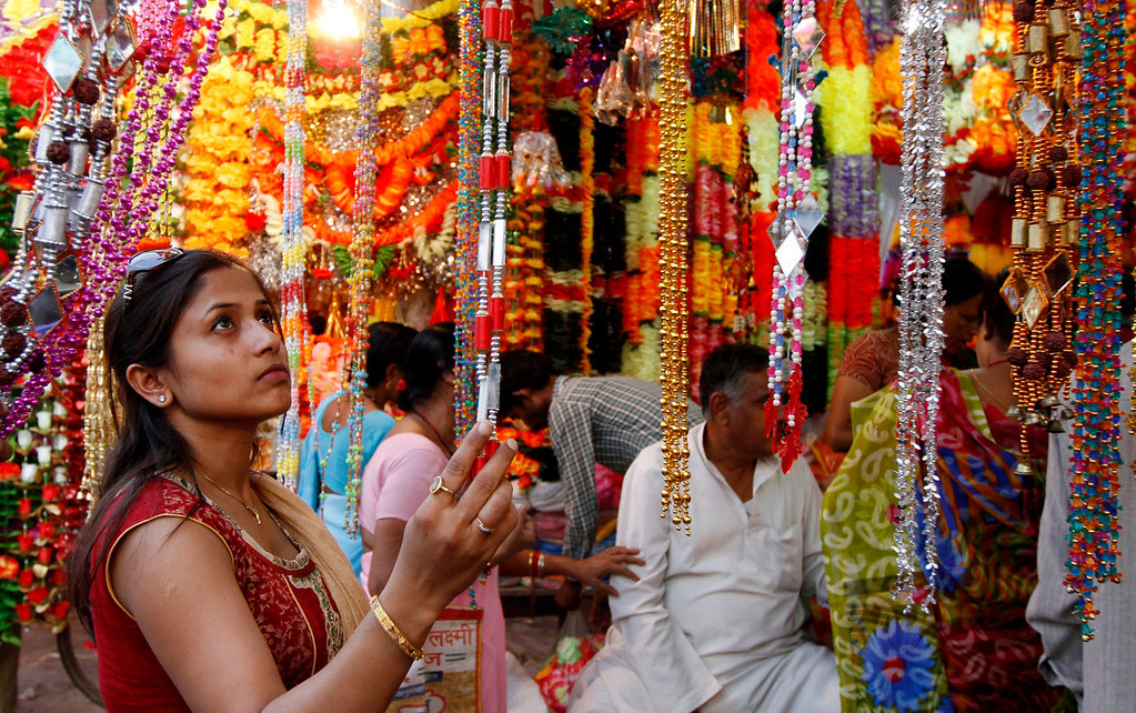 . An Indian woman shops for artificial garlands ahead of Diwali, the Hindu festival of lights, in Allahabad, India, Friday, Nov. 1, 2013. Hindus light up their homes and pray to Lakshmi, the goddess of wealth, during the festival which will be celebrated on Nov. 3. (AP Photo/ Rajesh Kumar Singh)