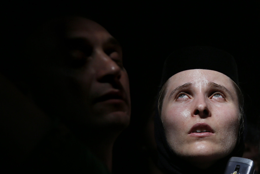 ". Christian Orthodox worshippers look up as a ray of light comes through a skylight in the Church of the Holy Sepulchre in Jerusalem\'s old city on April 19, 2014 during the ""Holy Fire\"" ceremony on the eve of the Orthodox Easter. AFP PHOTO/GALI TIBBON/AFP/Getty Images"