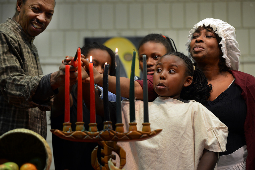 . Jimmy Walker, Kameelah Sims, Aliyah Fard and her sister Aminah Fard, and Roslyn Washington light candles following their performance during a Kwanzaa Celebration at the Zion Senior Center in Denver, CO, Saturday December, 29, 2012. The event highlighted the 150th anniversary of the Emancipation Proclamation with the groups theatrical performance depicting an enslaved family on Watch Night or Freedom\'s Eve, December 31, 1862. During the performance the family read the proclamation in anticipation of their coming freedom on New Years day, 1863. Craig F. Walker, The Denver Post