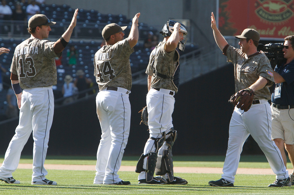 . San Diego Padres players congratulate each other after their 5-2 win over the Colorado Rockies in a baseball game on Sunday, Sept. 8, 2013, in San Diego. (AP Photo/Don Boomer)