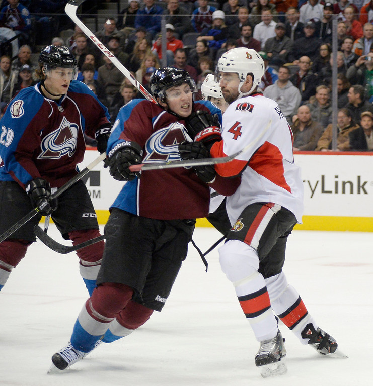 . Colorado Avalanche center Matt Duchene (9) gets pouched off the puck by Ottawa Senators defenseman Chris Phillips (4) during the third period January 8, 2014 at Pepsi Center. (Photo by John Leyba/The Denver Post)