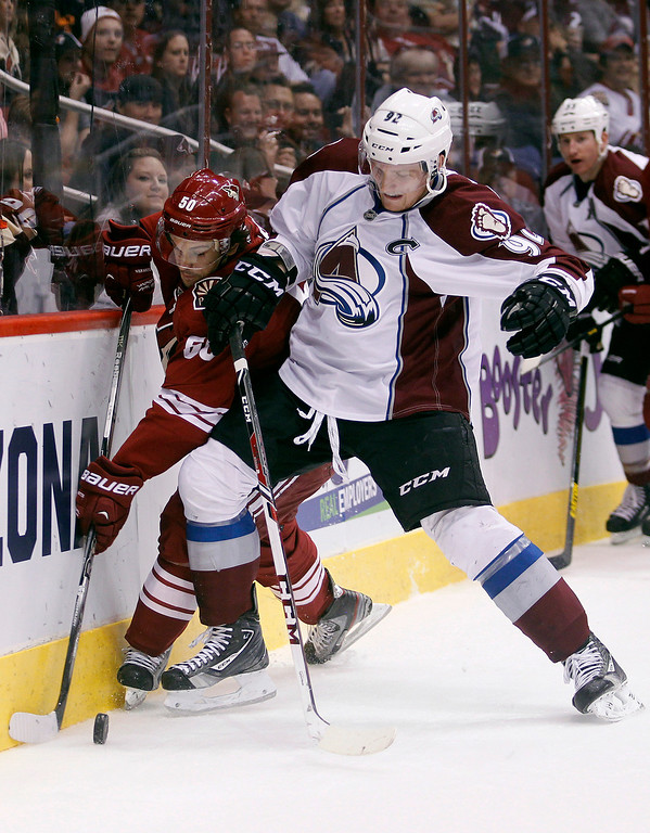 . Phoenix Coyotes center Antoine Vermette, left, and Colorado Avalanche left winger Gabriel Landeskog, right, of Sweden, battle for the loose puck in the first period of NHL hockey game, Saturday, April 6, 2013, in Glendale, Ariz. (AP Photo/Paul Connors)