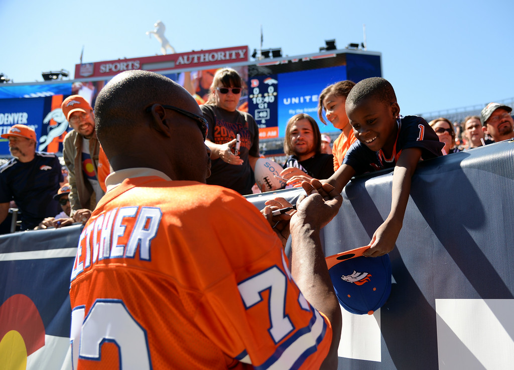 . Former Denver Broncos Simon Fletcher, front, signs autographs to the fans during the Broncos scrimmage at Sports Authority Field at Mile High. Denver, Colorado. August 02. 2014. (Photo by Hyoung Chang/The Denver Post)