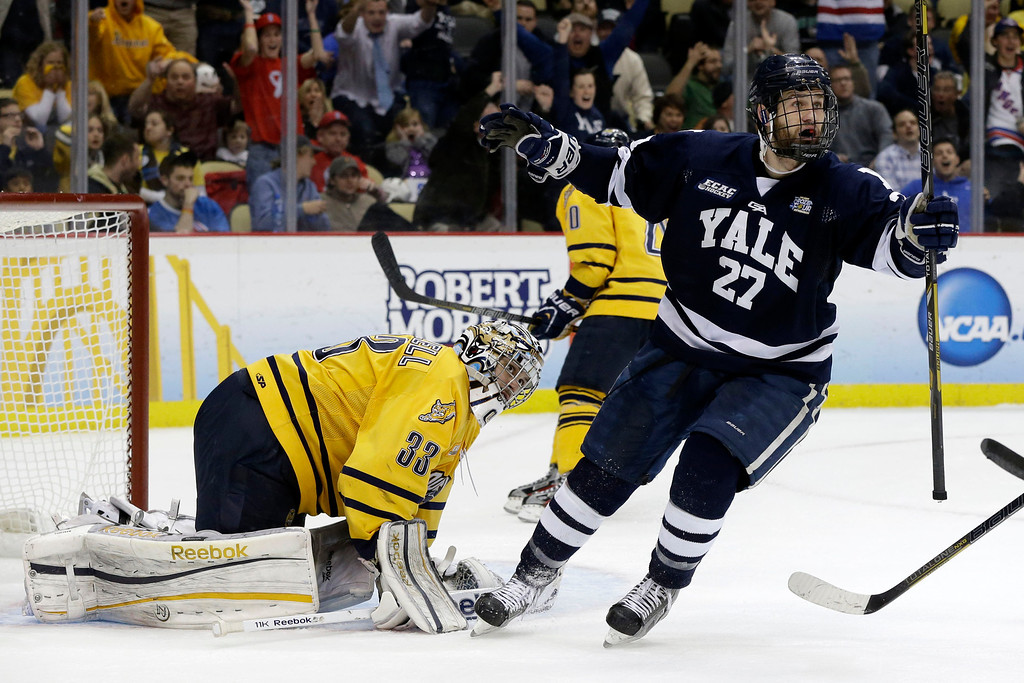 . Yale\'s Charles Orzetti (27) celebrates a first-period goal by teammate Clinton Bourbonais (not shown) past Quinnipiac goalie Eric Hartzell (33) during the first period of the NCAA men\'s college hockey national championship game in Pittsburgh, Saturday, April 13, 2013. (AP Photo/Gene Puskar)