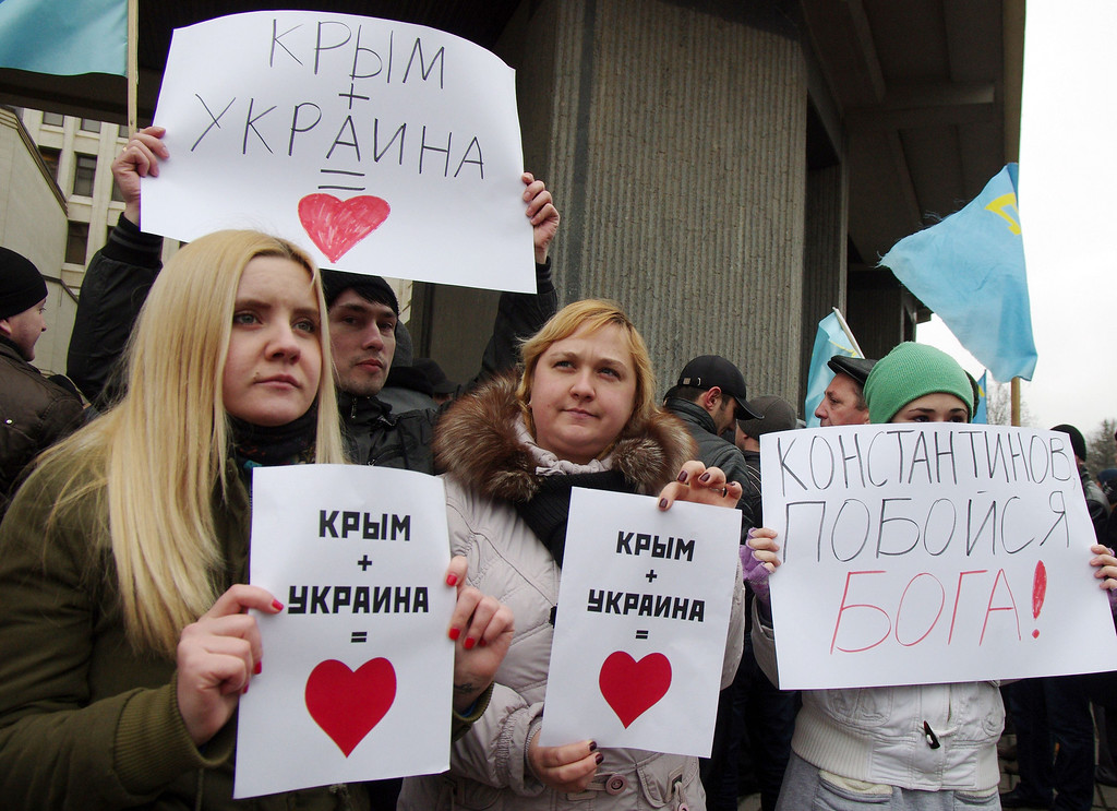 ". Pro-Ukrainian activists hold placards reading ""Crimea+Ukraine is love\"" during a rally in front of the Crimean parliament in Semfiropol on February 26, 2014. Pro-Russian demonstrators on Wednesday brawled with supporters of Ukraine\'s new interim authorities in the capital of the Russophone Crimea region Simferopol, an AFP reporter at the scene said. Scuffles erupted as thousands of pro-Moscow residents and Muslim Crimean Tatars backing the new leadership in Kiev held competing rallies outside the regional parliament building, where local legislators rejected demands to debate splitting from Kiev.  Vasiliy BATANOV/AFP/Getty Images"