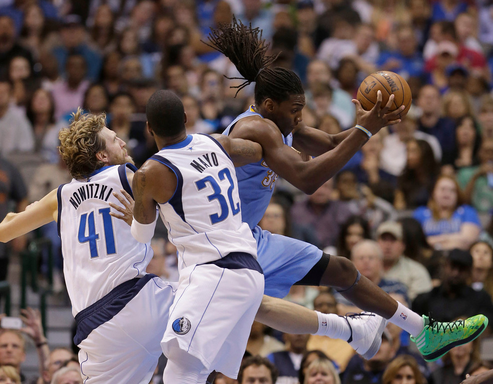 . Denver Nuggets small forward Kenneth Faried (35) is defended by Dallas Mavericks power forward Dirk Nowitzki (41), of Germany, and shooting guard O.J. Mayo (32) during overtime play of an NBA basketball game on Friday, April 12, 2013, in Dallas. The Mavericks won 108-105. (AP Photo/LM Otero)