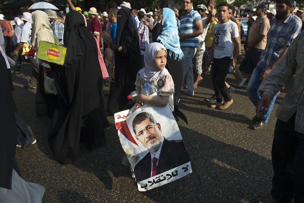 . An Egyptian girl holds a portrait of Egypt\'s ousted president Mohammed Morsi during a march in Ramssis street in Cairo on August 12, 2013. Egypt\'s judiciary extended ousted president Mohamed Morsi\'s detention as his supporters marched through Cairo in defiance of the expiry of a government ultimatum to dismantle their huge protest camps.  KHALED DESOUKI/AFP/Getty Images
