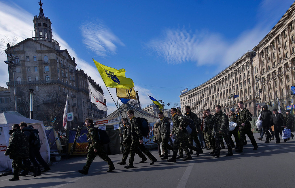 . Ukrainian volunteers, members of the self defense forces of Maidan, march with flags and luggage before their deployment at a training facility, at the Independence Square in Kiev, Ukraine, 14 March 2014. These volunteers are going to receive proper military training outside Kiev. Ukraine\'s Parliament backed on 13 March the creation of a new National Guard of 60,000 volunteers to supplement its conventional army forces, consisting of 130,000 soldiers. Ukrainian volunteers crowded the recruitment centers in response to the mobilization call, related to the Russian maneuvers in Crimean peninsula. The USA and European Union have threatened sanctions against Moscow over the military standoff in the strategic Crimean peninsula, and are urging Russia to pull back its forces in the region and allow in international observers and human rights monitors. Crimea, which has a majority ethnic Russian population, is strategically important to Russia as the home port of its Black Sea Fleet.  EPA/ROBERT GHEMENT