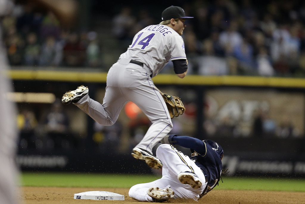 . MILWAUKEE, WI - APRIL 2: Josh Rutledge #14 of the Colorado Rockies turns the double play while Rickie Weeks #23 of the Milwaukee Brewers slides into second base during the bottom of the first inning at Miller Park on April 2, 2013 in Milwaukee, Wisconsin. (Photo by Mike McGinnis/Getty Images)