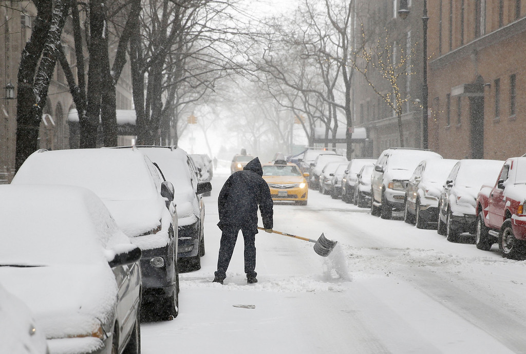 . A man shovels snow into the street in the Manhattan borough of New York, Tuesday, Jan. 21, 2014.  The National Weather Service said the storm could bring 10 to 14 inches of snow to Philadelphia and southern New England and up to a foot in New York City, to be followed by bitter cold. An arctic air mass will plunge the eastern half of the United States into a deep freeze, with wind chills as low as 40 degrees below zero, the weather service said. (AP Photo/Seth Wenig)