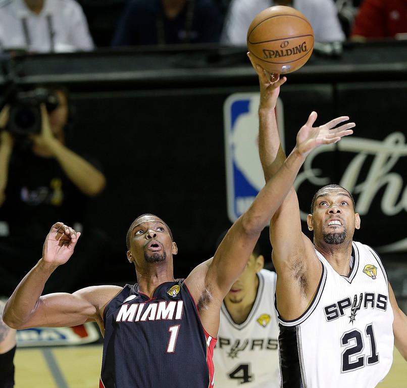 . Miami Heat\'s Chris Bosh(1) and San Antonio Spurs\' Tim Duncan (21) take the tip to begin Game 5 of the NBA Finals basketball series, Sunday, June 16, 2013, in San Antonio. (AP Photo/David J. Phillip)
