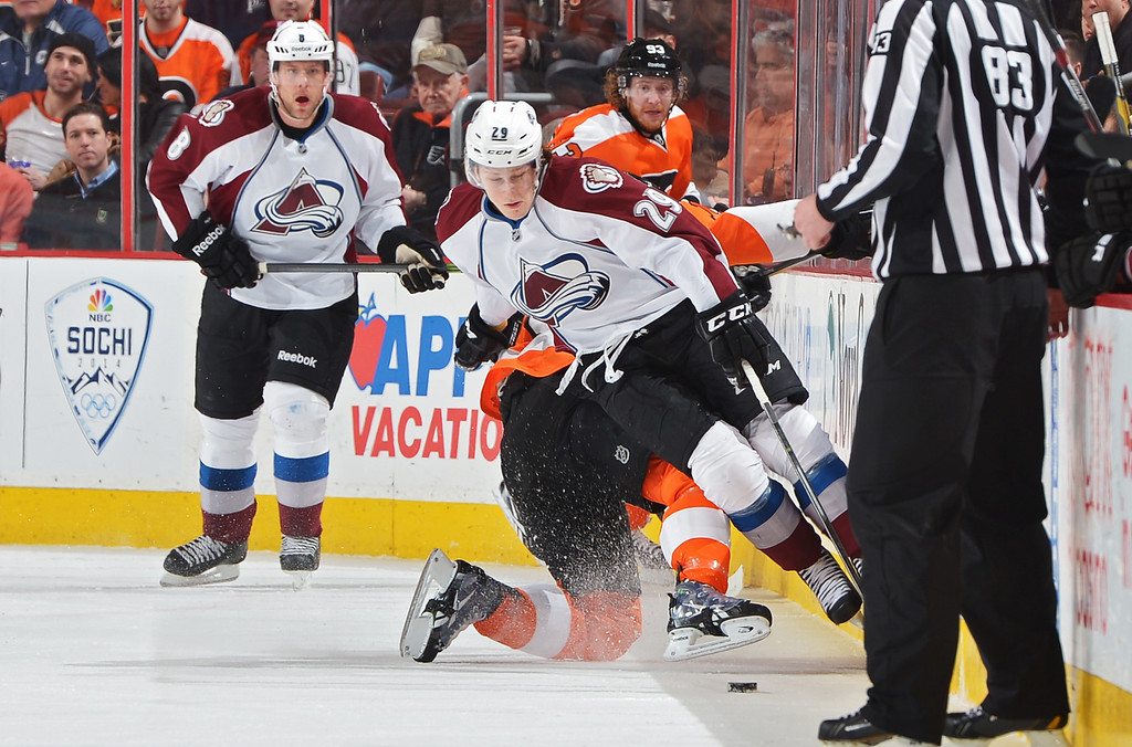 . PHILADELPHIA, PA - FEBRUARY 06: Nathan MacKinnon #29 of the Colorado Avalanche gets knocked to the ice by Scott Hartnell #19 of the Philadelphia Flyers at the Wells Fargo Center on February 6, 2014 in Philadelphia, Pennsylvania.  (Photo by Drew Hallowell/Getty Images)