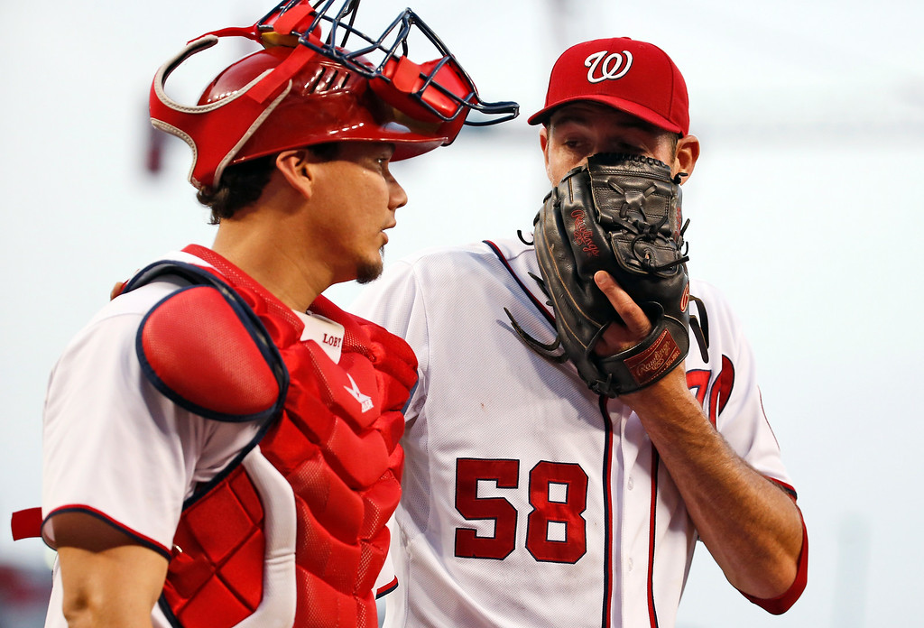 . Washington Nationals starting pitcher Doug Fister (58) talks with catcher Jose Lobaton as they walk to the dugout during the fifth inning of a baseball game against the Colorado Rockies at Nationals Park, Wednesday, July 2, 2014, in Washington. (AP Photo/Alex Brandon)