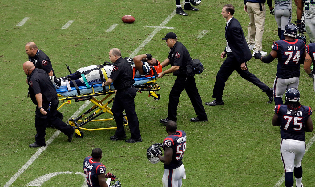 . Seattle Seahawks\' Michael Bennett is carted off the field after he was injured during the second quarter an NFL football game against the Houston Texans, Sunday, Sept. 29, 2013, in Houston. (AP Photo/David J. Phillip)
