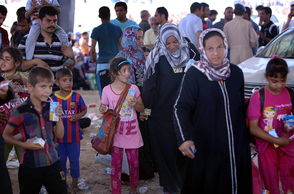 . Iraqi families fleeing violence in the northern Nineveh province gather at a Kurdish checkpoint in Aski kalak, 40 kms West of Arbil, in the autonomous Kurdistan region, on June 10, 2014. Suspected jihadists seized Iraq\'s entire northern province of Nineveh and its capital Mosul, the country\'s second-largest city, in a major blow to authorities, who appear incapable of stopping militant advances.  SAFIN HAMED/AFP/Getty Images