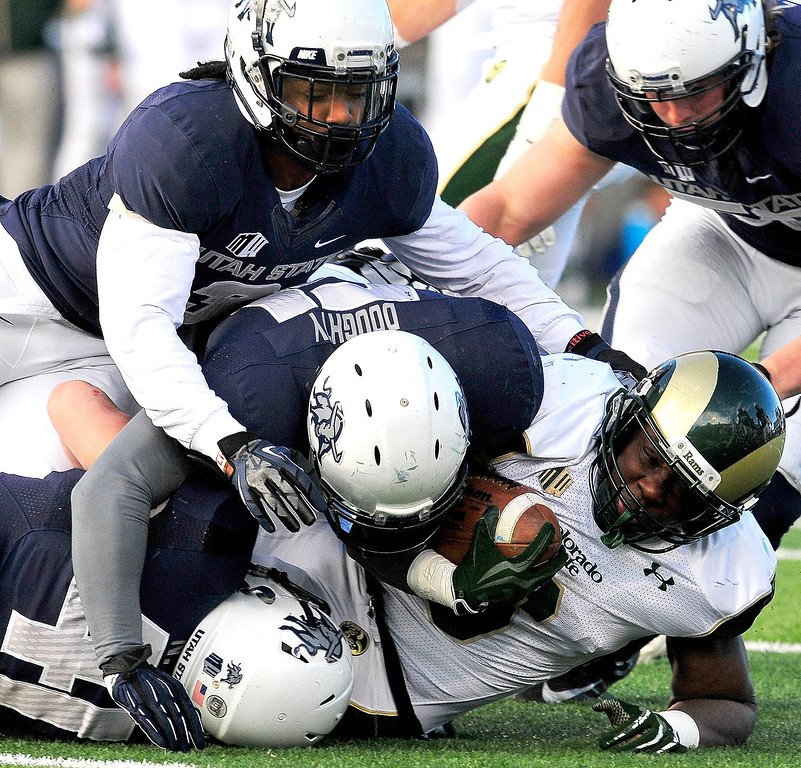 . Colorado State\'s Chris Nwoke (6) gets tackled by Utah State\'s Nick Vigil (41), Jake Doughty (51) and Quinton Byrd (3) during an NCAA college football game, Saturday, Nov. 23, 2013, in Logan, Utah. Utah State won 13-0. (AP Photo/Herald Journal, John Zsiray)