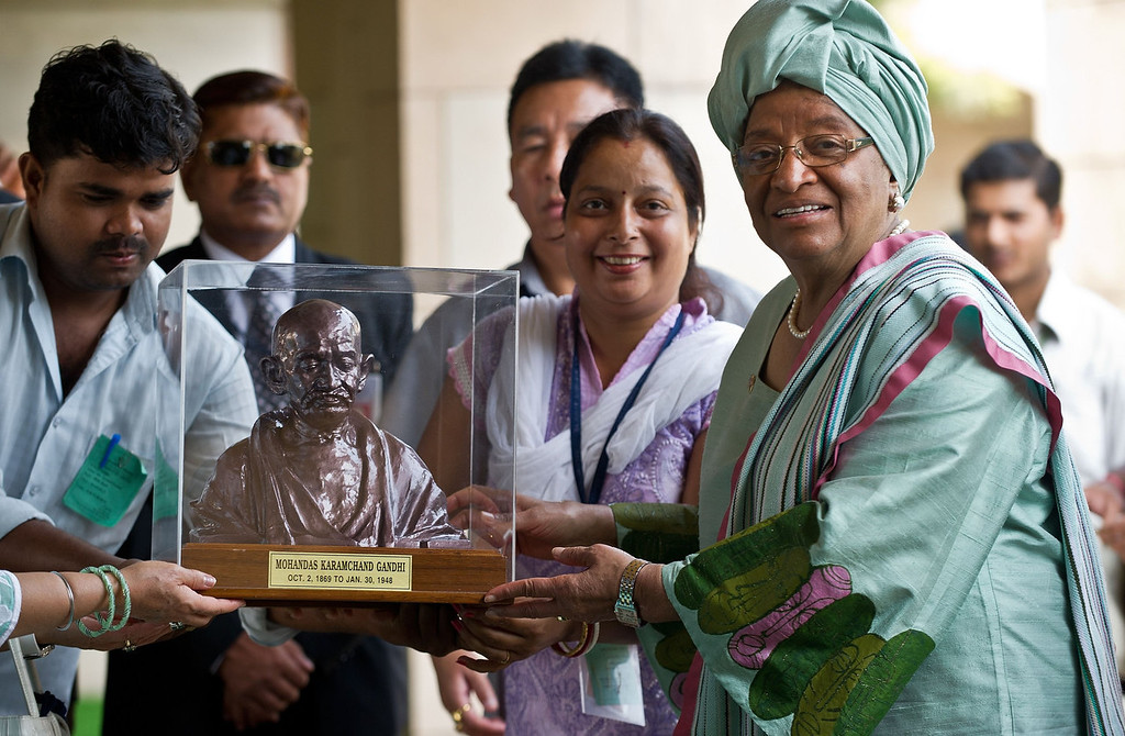 . President of the Republic of Liberia Ellen Johnson-Sirleaf (R) receives a memento at Rajghat, memorial for Mahatma Gandhi, during a visit in New Delhi on September 11, 2013.  Johnson-Sirleaf is in India for a five-day state visit.  PRAKASH SINGH/AFP/Getty Images
