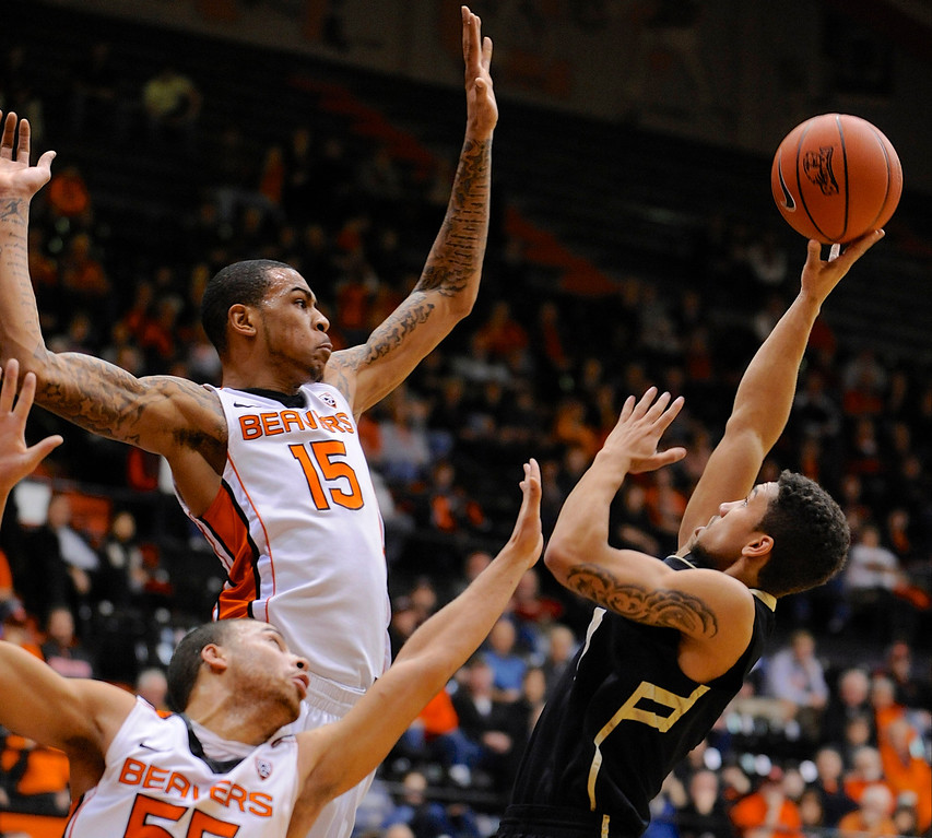 . Colorado\'s Askia Booker, right, shoots against Oregon State\'s Eric Moreland (15) and Roberto Nelson (55) during the first half of an NCAA college basketball game in Corvallis, Ore., Sunday, Feb. 10, 2013. (AP Photo/Greg Wahl-Stephens)