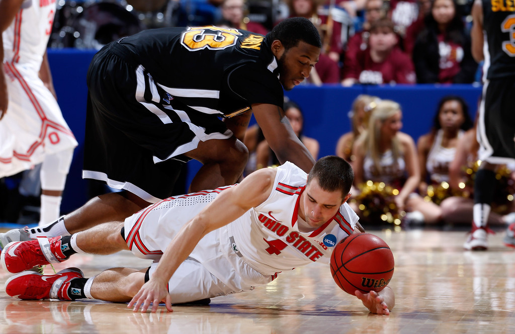 . DAYTON, OH - MARCH 22: Aaron Craft #4 of the Ohio State Buckeyes and David Laury #13 of the Iona Gaels dive for a loose ball in the second half during the second round of the 2013 NCAA Men\'s Basketball Tournament at UD Arena on March 22, 2013 in Dayton, Ohio.  (Photo by Joe Robbins/Getty Images)