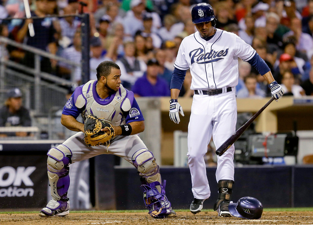 . Colorado Rockies catcher Wilin Rosario, left, looks toward the San Diego Padres\' runner on third base after retrieving a pitch that bounced away as Padres\' batter Jesus Guzman, right, steps out of the way in the third inning of a baseball game in San Diego, Tuesday, July 9, 2013. (AP Photo/Lenny Ignelzi)