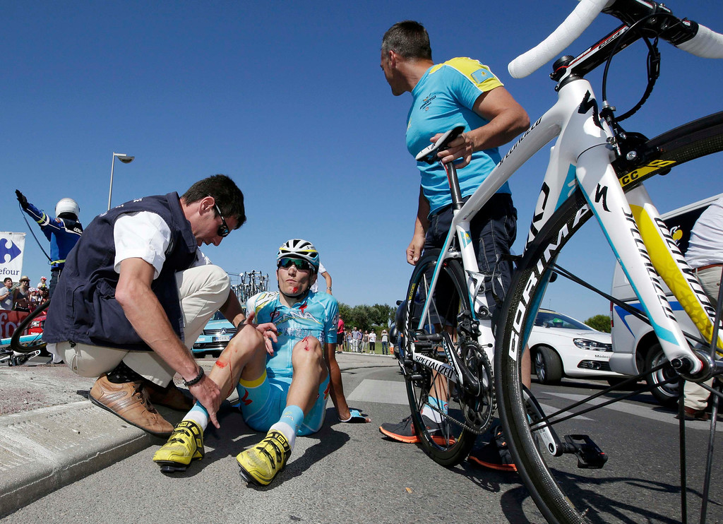 . Astana team rider Janez Brajkovic of Slovakia receives medical care after he fell during the 176.5 km fifth stage of the centenary Tour de France cycling race from Aix-En-Provence to Montpellier July 4, 2013.    REUTERS/Jacky Naegelen