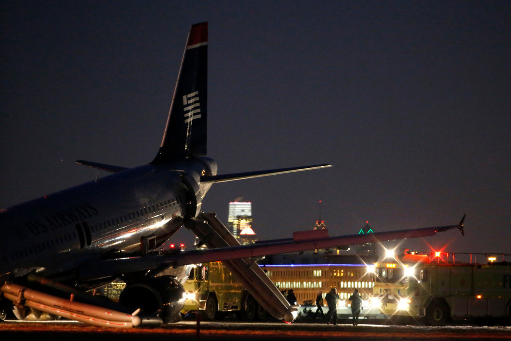 . Investigators work near a damaged US Airways jet at the end of a runway at the Philadelphia International Airport, Thursday, March 13, 2014, in Philadelphia. Airline officials said the flight was heading to Fort Lauderdale, Fla., when the pilot was forced to abort takeoff around 6:30 p.m., after the front landing gear failed. An airport spokeswoman said no injuries have been reported. (AP Photo/Matt Slocum)