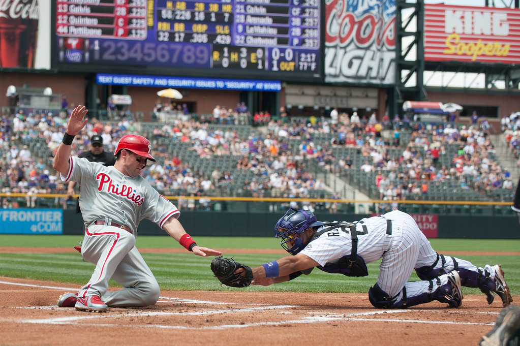. DENVER, CO - JUNE 15:  Michael Young #10 of the Philadelphia Phillies is tagged out by Wilin Rosario #20 of the Colorado Rockies on a close play at home plate on a double by Ryan Howard #6 of the Philadelphia Phillies (not pictured) in the first inning of a game at Coors Field on June 15, 2013 in Denver, Colorado.  (Photo by Dustin Bradford/Getty Images)