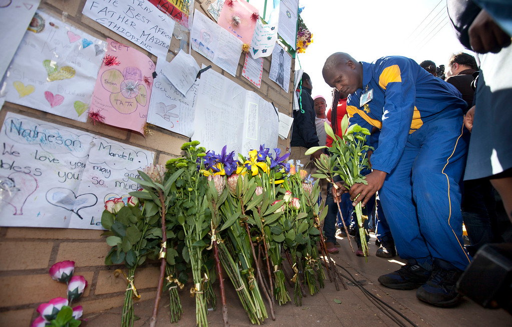 """. A group of police cadets from Pretoria leave flowers outside the entrance to the Mediclinic Heart Hospital where former South African President Nelson Mandela is being treated in Pretoria, South Africa Tuesday, June 25, 2013. South Africans passed by Nelson Mandela\'s home in a Johannesburg suburb on Tuesday and said they were praying for the 94-year-old after the president Jacob Zuma urged the country to send their wishes to the man he called the \""""father of democracy,\"""" who remained in critical condition. (AP Photo/Ben Curtis)"""