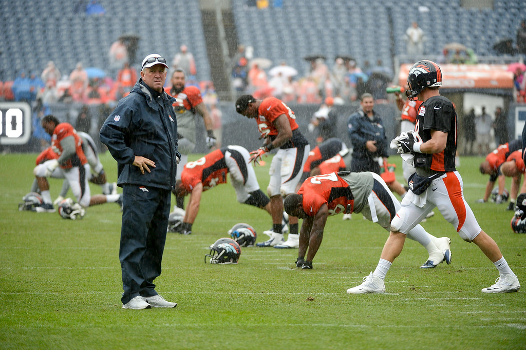 . Denver Broncos head coach John Fox watches the team stretch during a rain day on day six of the Denver Broncos 2014 training camp July 30, 2014 at Sports Authority Field at Mile High Stadium.  (Photo by John Leyba/The Denver Post)