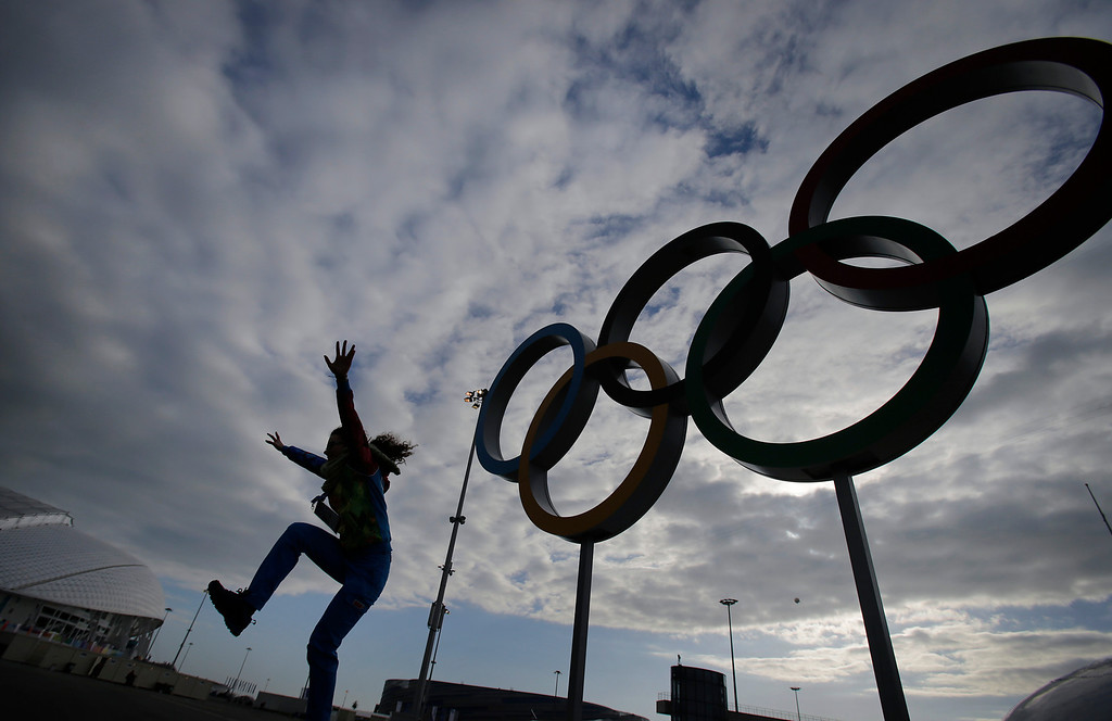 . Sigita Mazonaite, 24, a volunteer from Lithuania leaps as she is photographed by her friend, in front of the Olympic rings ahead of the 2014 Winter Olympics, Tuesday, Feb. 4, 2014, in Sochi, Russia. (AP Photo/Wong Maye-E)