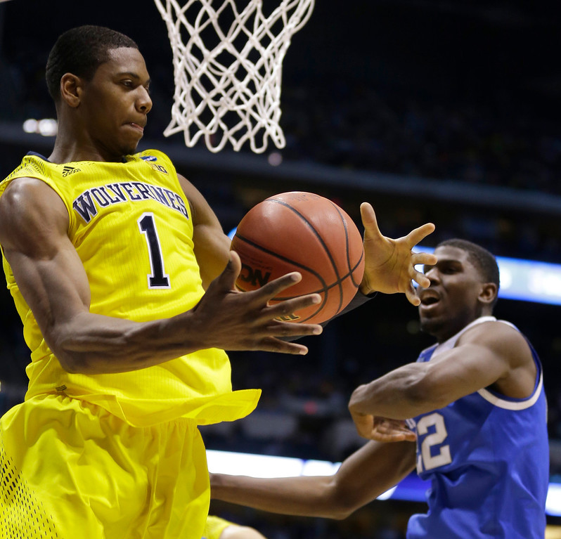 . Michigan\'s Glenn Robinson III (1) grabs a rebound in front of Kentucky\'s Alex Poythress (22) during the first half of an NCAA Midwest Regional final college basketball tournament game Sunday, March 30, 2014, in Indianapolis. (AP Photo/Michael Conroy)
