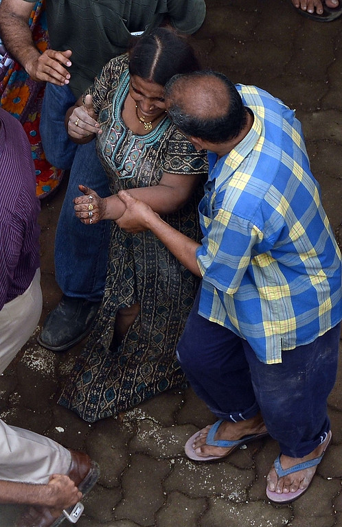. A female survivor is comforted by a neighbor while being taken to an awaiting ambulance at the site of a building collapse in Mumbai on September 27, 2013.  AFP PHOTO/Indranil MUKHERJEE/AFP/Getty Images