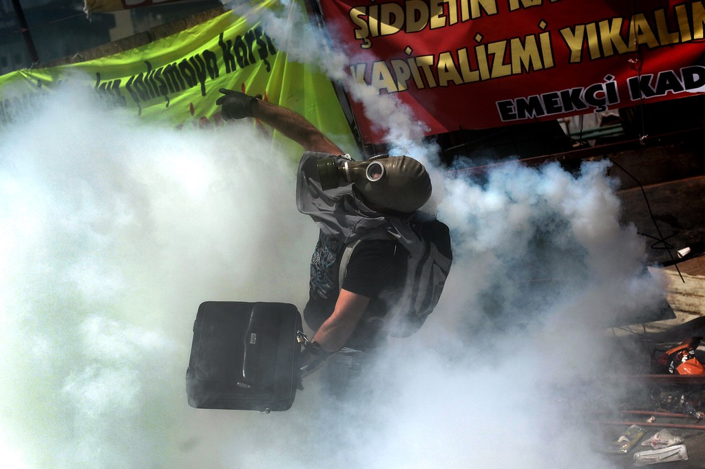 . A protester wearing a gas mask, throws back a tear gas canister during clashes with riot police in Istanbul\'s Taksim square on June 11, 2013. AFP PHOTO / ARIS MESSINIS/AFP/Getty Images
