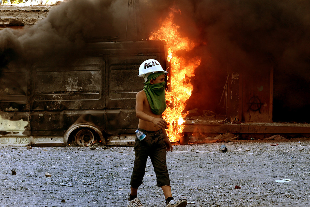 . A young protester passes a burning vehicle at Taksim square in Istanbul on June 11, 2013. AFP PHOTO / ARIS  MESSINIS/AFP/Getty Images