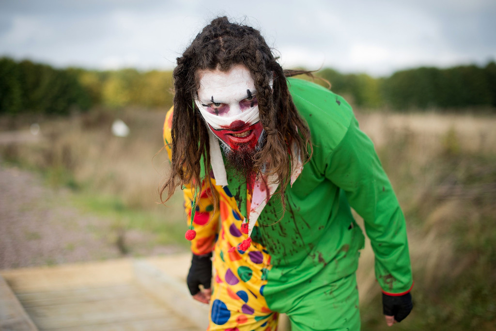 ". A zombie clown prepares for the runners as he takes part in one of Britain\'s biggest horror events, the ""Zombie Evacuation Race\"" at Carver Barracks near Saffron Walden, England, on October 5, 2013. The race sees thousands of participants attempt to complete a gruelling 5 kilometre cross-country run, while evading \""zombies\"", intent on snatching the three life-line strips hanging from every runner\'s waist.  Those who manage to get through with any strips remaining are named as survivors while those without take home an \""infected\"" badge.  LEON NEAL/AFP/Getty Images"