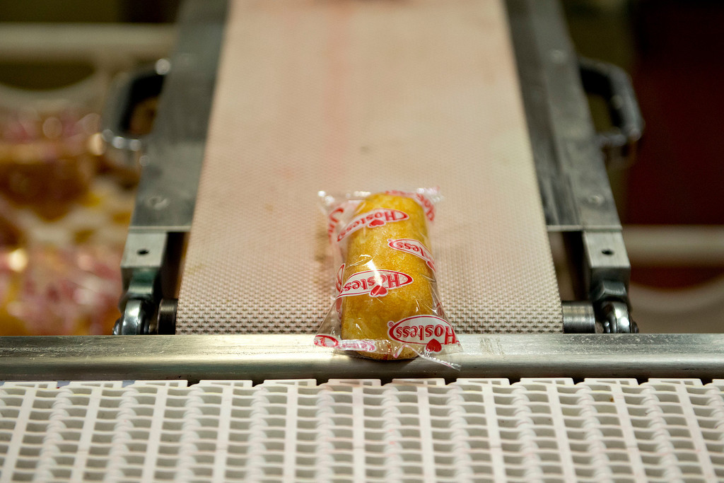 . A Hostess Brands LLC Twinkies snack cake travels on a conveyor belt in the packaging area of the company\'s bakery in Schiller Park, Illinois, U.S., on Monday, July 15, 2013. Photographer: Daniel Acker/Bloomberg