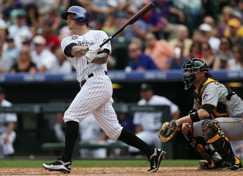 . Colorado Rockies\' Brandon Barnes, left, follows the flight of his two-run home run with Pittsburgh Pirates catcher Chris Stewart in the fourth inning of a baseball game in Denver on Sunday, July 27, 2014. (AP Photo/David Zalubowski)