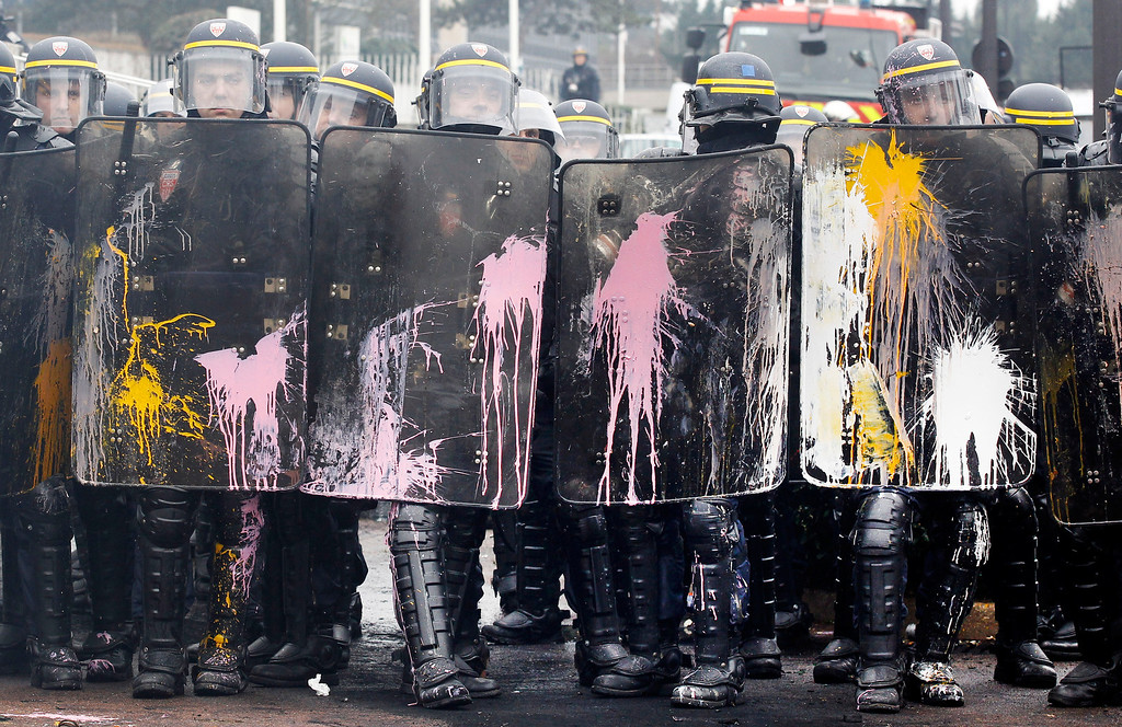 . Riot policemen protect themselves during a demonstration against layoffs by Goodyear employees, at the Goodyear headquarters in Rueil Malmaison, west of Paris, Thursday March 7, 2013.  (AP Photo/Remy de la Mauviniere)